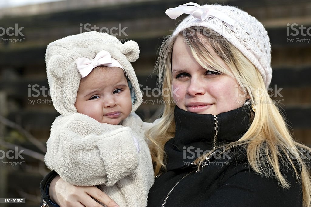 Young teenage mother with her baby standing outside royalty-free stock photo