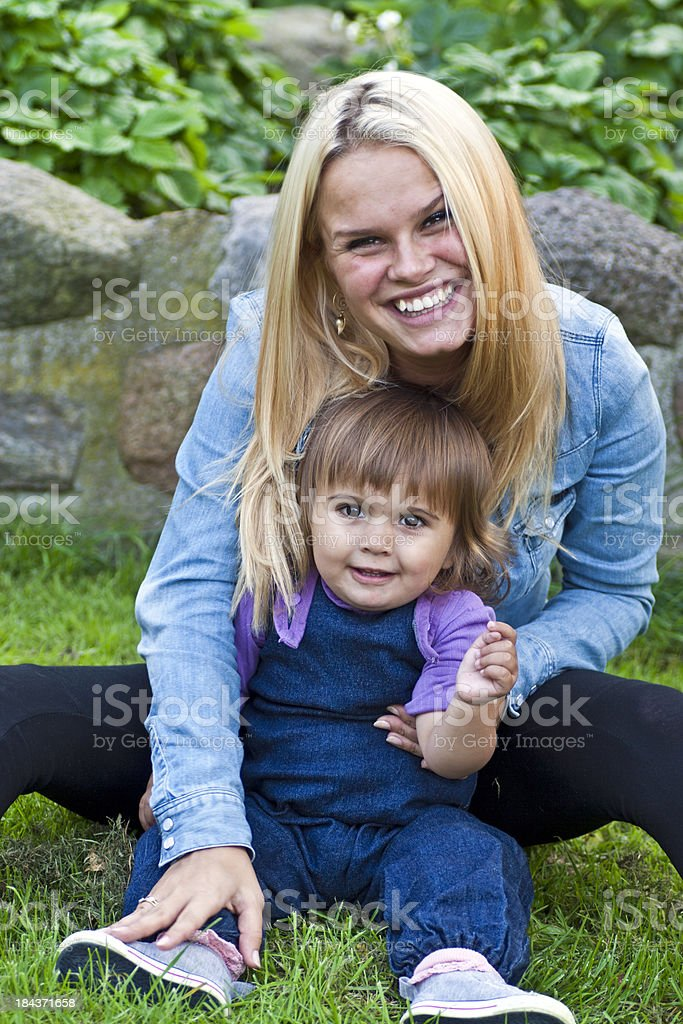 Young teenage mother with her child sitting in the grass royalty-free stock photo