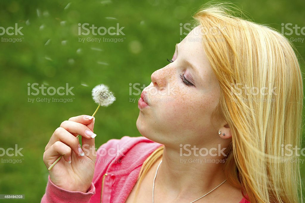 Young teenager blowing a dandelion royalty-free stock photo