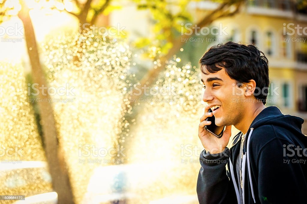 Young Teenager having a cheerful conversation on phone stock photo