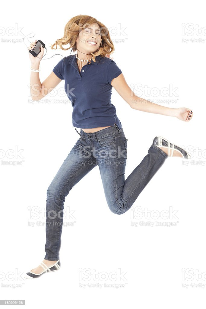 Young Teenager Jumping in the Air Listening to Music royalty-free stock photo
