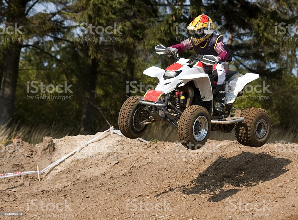 Young teenager jumping on his white new quad bike stock photo