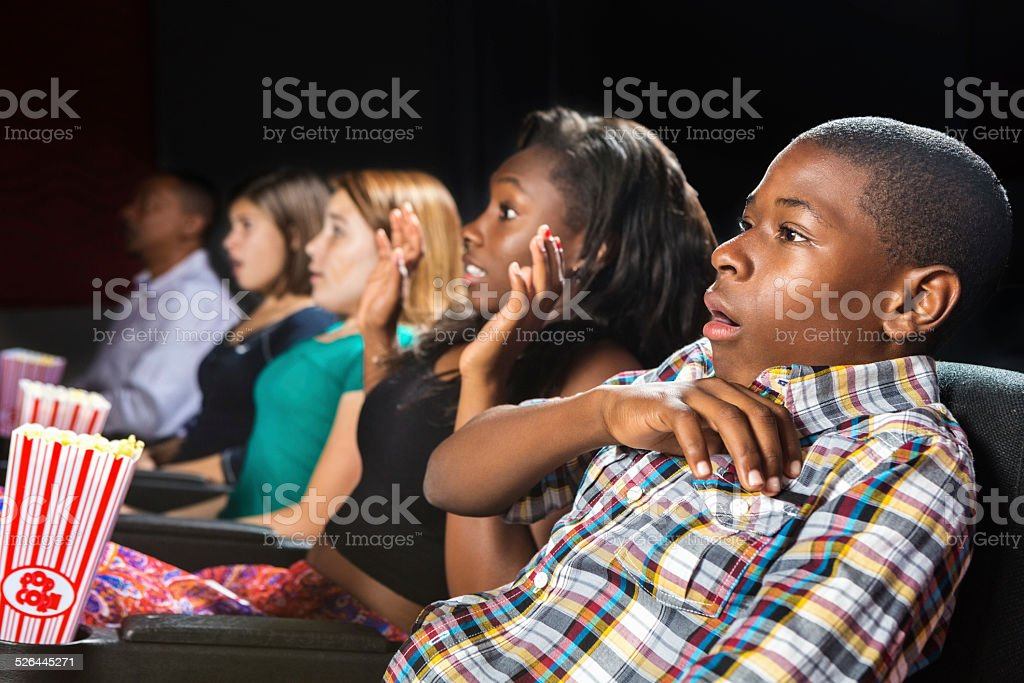 Young teens scared by movie in local theater stock photo