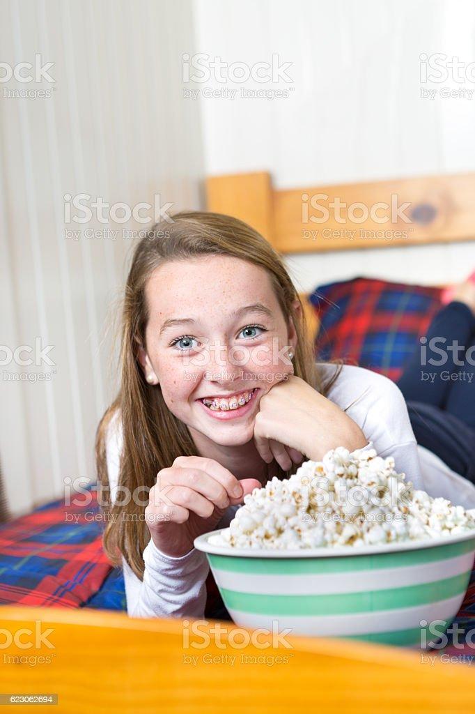 Young Ten Girl in Her Bedroom Watching TV with Popcorn stock photo
