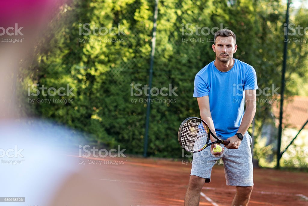 Young tennis player about to serve ball on tennis court. stock photo