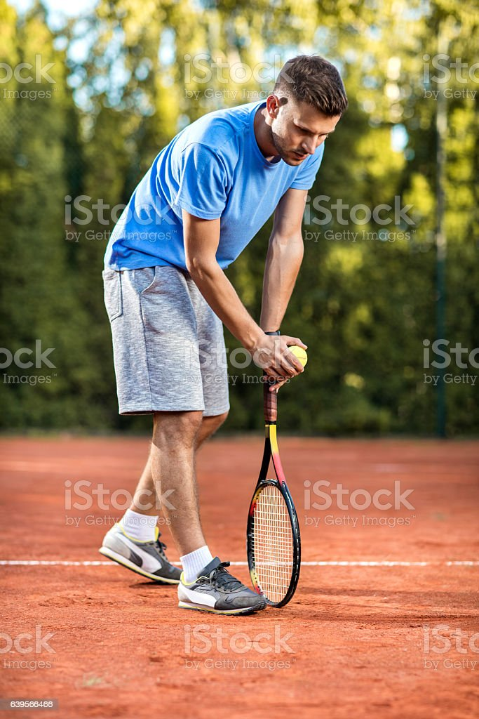 Young tennis player preparing to serve the ball during match. stock photo