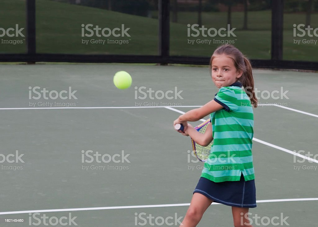Young tennis player preparing to swing at the green ball royalty-free stock photo