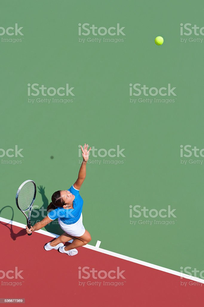 Young tennis player serving stock photo