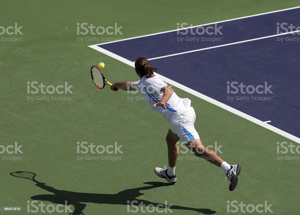 Young tennis player stretching to hit a tennis ball stock photo