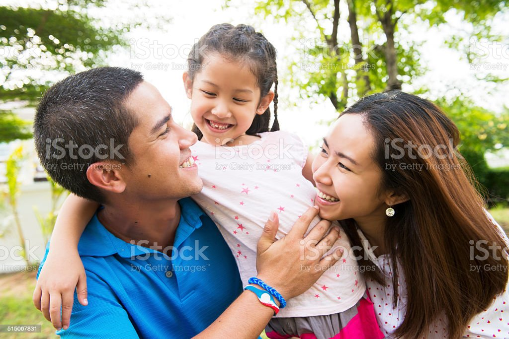 Young Thai Family Spending Time in Front of Home stock photo
