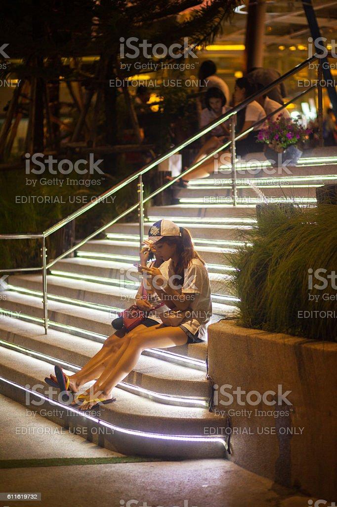 Young thai girls on illuminated steps and sidewalk stock photo