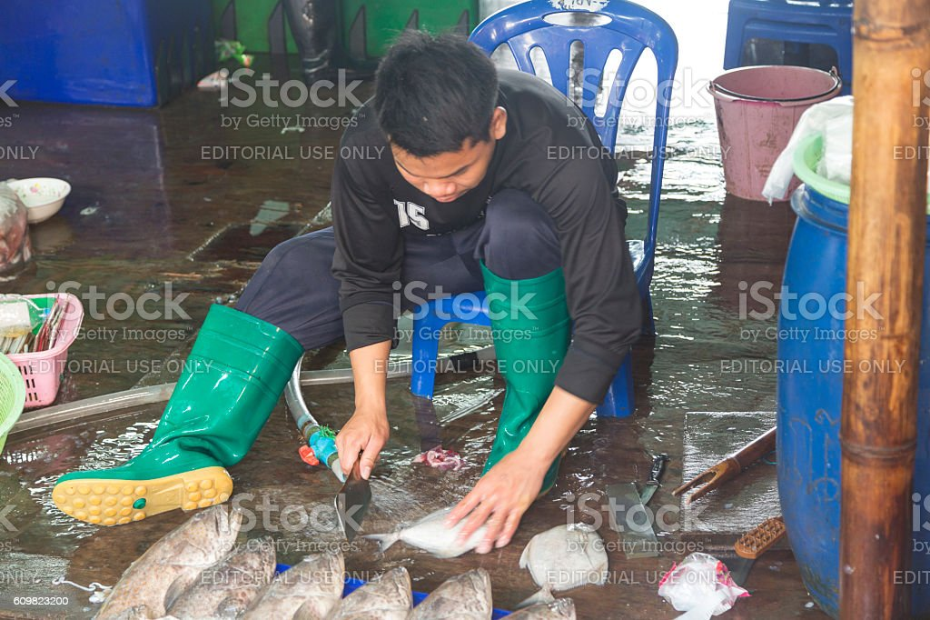 Young Thai man cleaning fish at the outdoor market stock photo