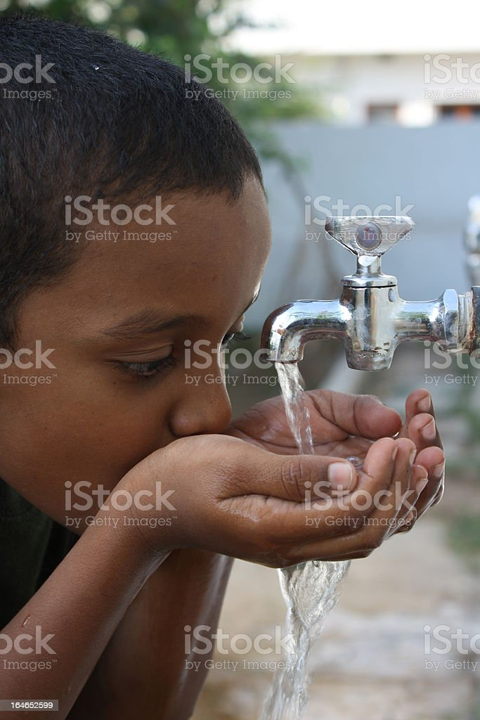 Young thirsty boy drinking water from the faucet stock photo