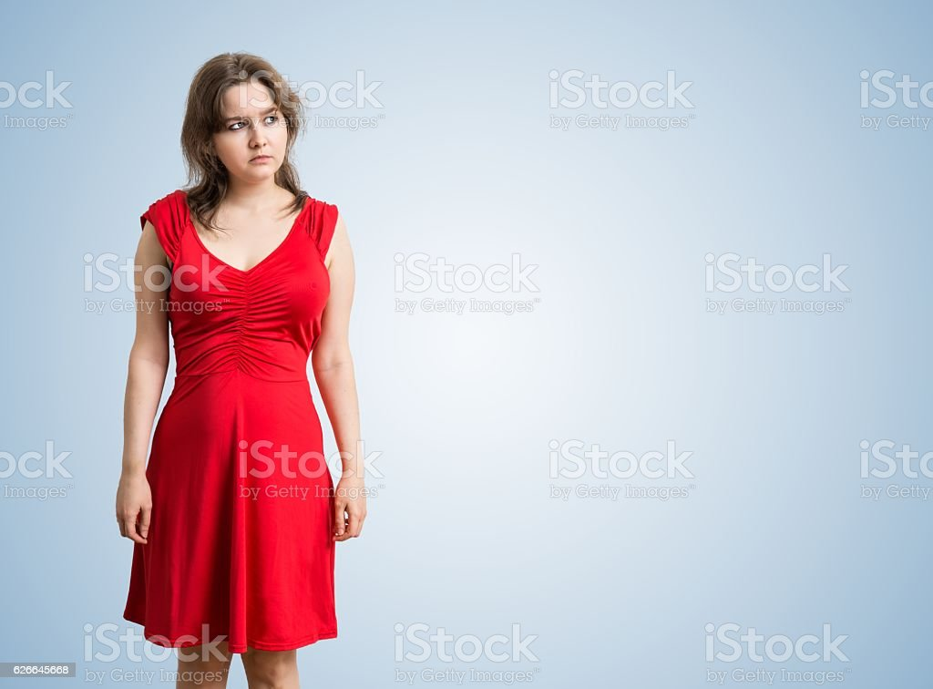 Young thoughtful and sad woman is thinking on blue background. stock photo