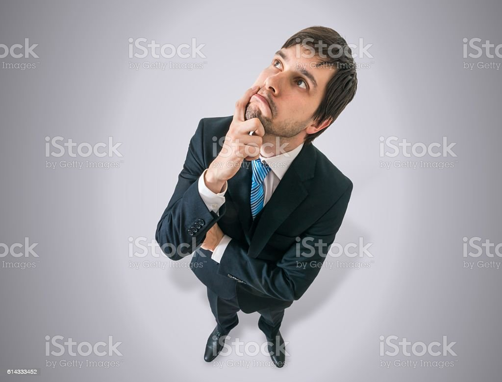 Young thoughtful  businessman is thinking. View from top. stock photo