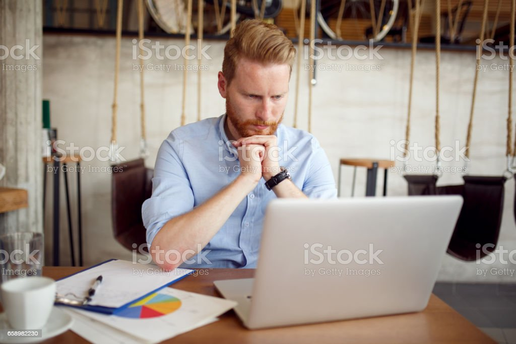 Young thoughtful businessman using laptop during coffee break. stock photo