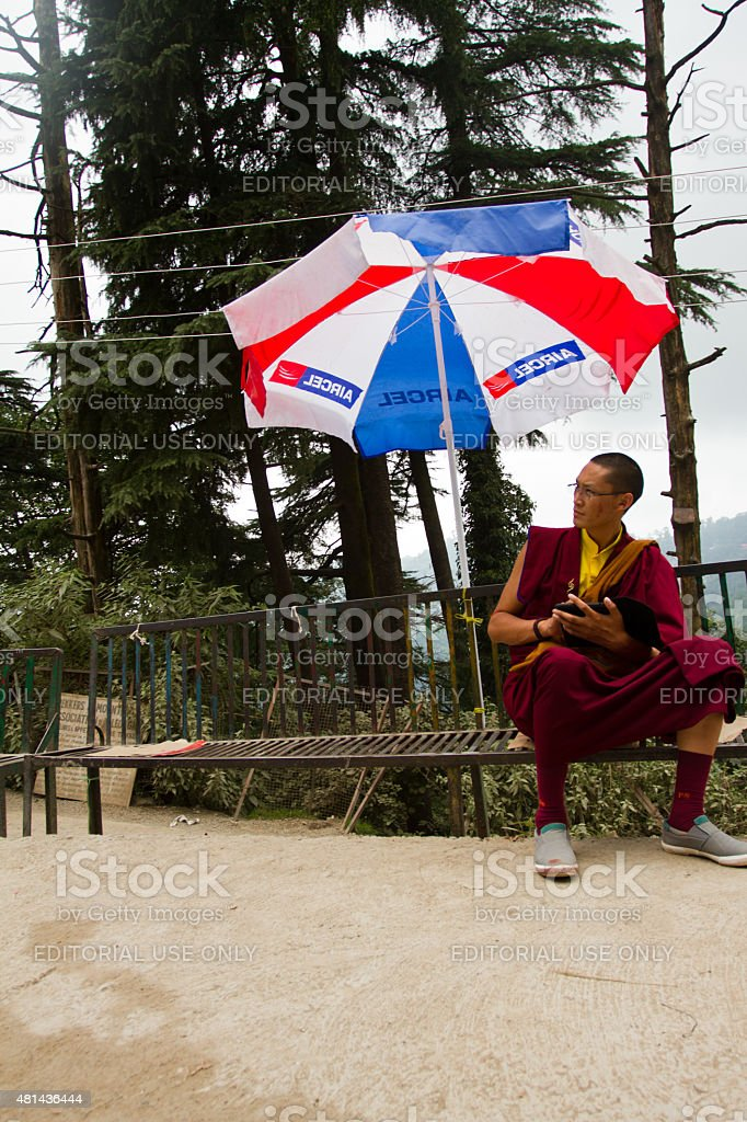 Young Tibetan Buddhist with an umbrella stock photo