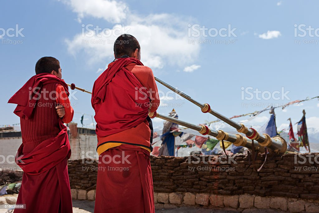 Young Tibetan monks playing buddhist horns on the roof, Mustang stock photo