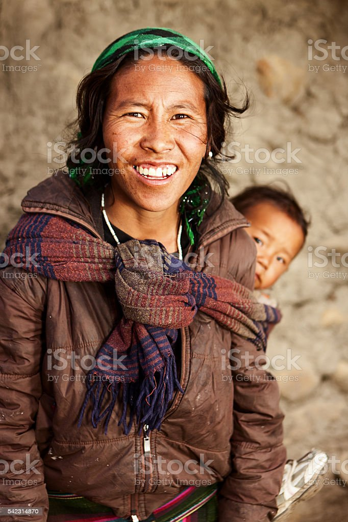 Young Tibetan mother carrying her child stock photo