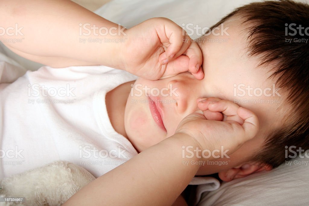 A young, tired boy rubbing his eyes royalty-free stock photo