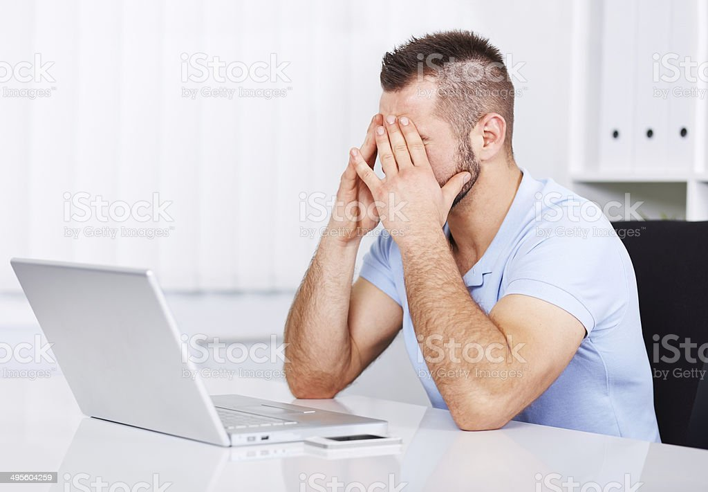 Young tired businessman rubbing his eyes stock photo