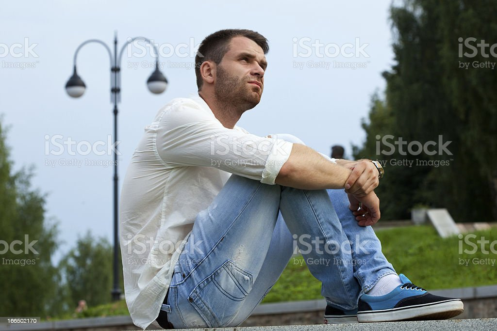 Young tired man sit on border in summer park royalty-free stock photo