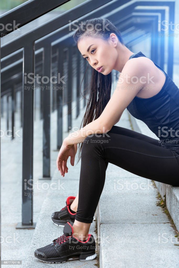 Young tired sportswoman in sportswear sitting on stadium stairs stock photo