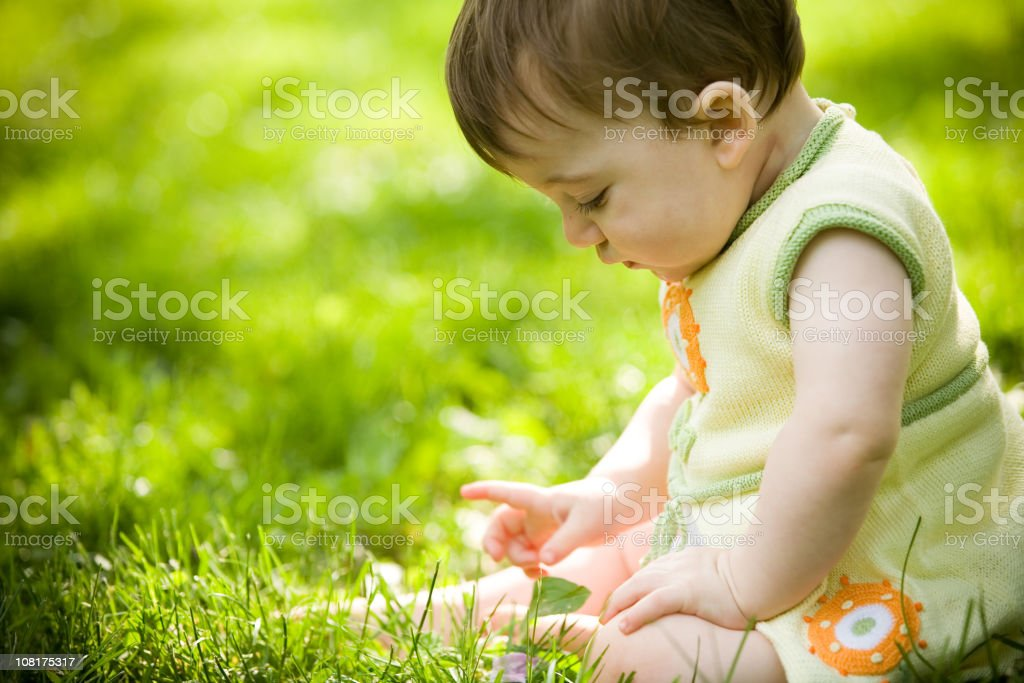 Young toddler girl sitting in grass on a sunny day royalty-free stock photo
