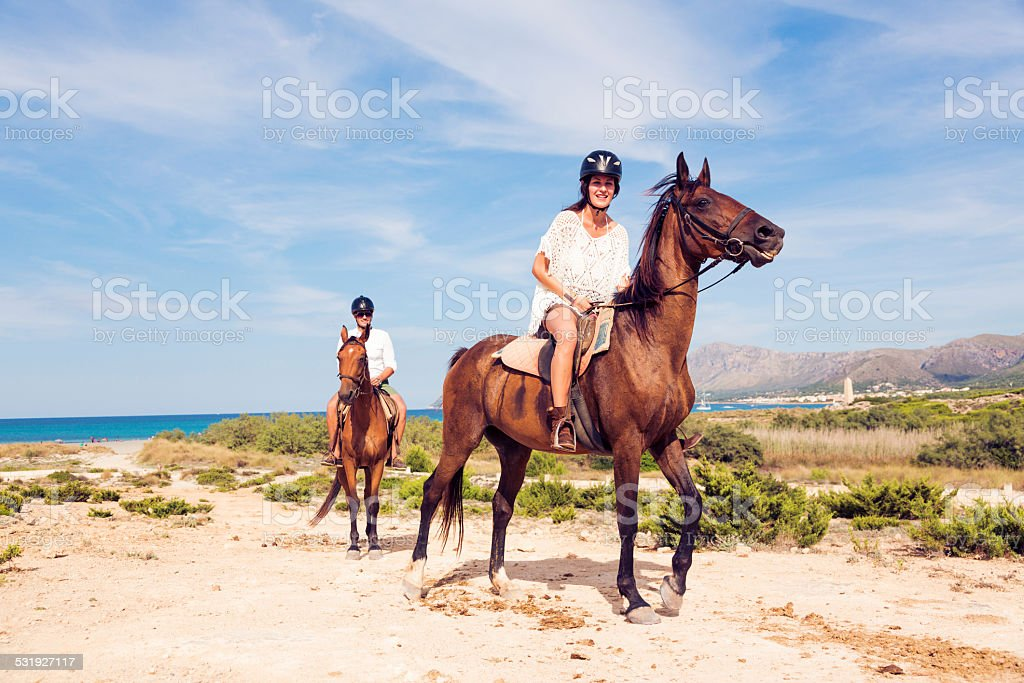young tourist couple horseback riding stock photo