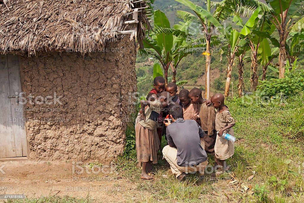 Young tourist showing Ugandan children photos on digicam stock photo