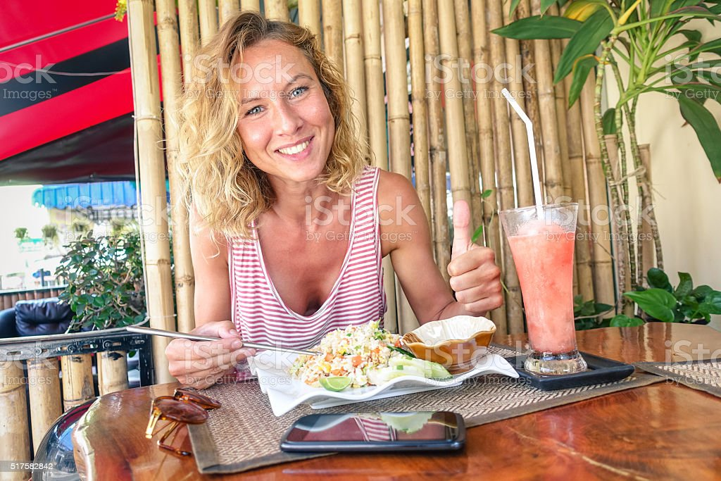 Young tourist woman eating fried rice and drinking fruit smoothie stock photo