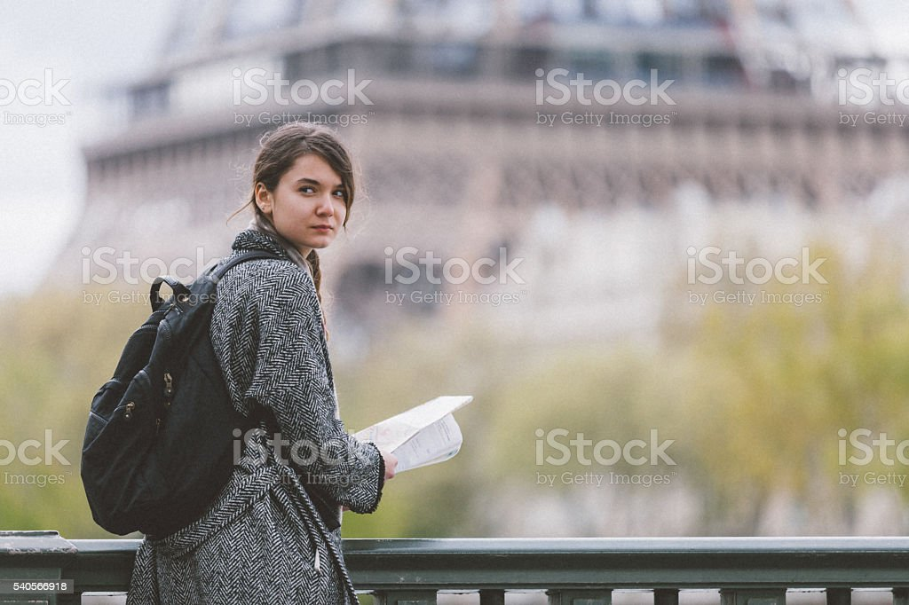 Young tourist woman reading Paris city map against Tour Eiffel stock photo