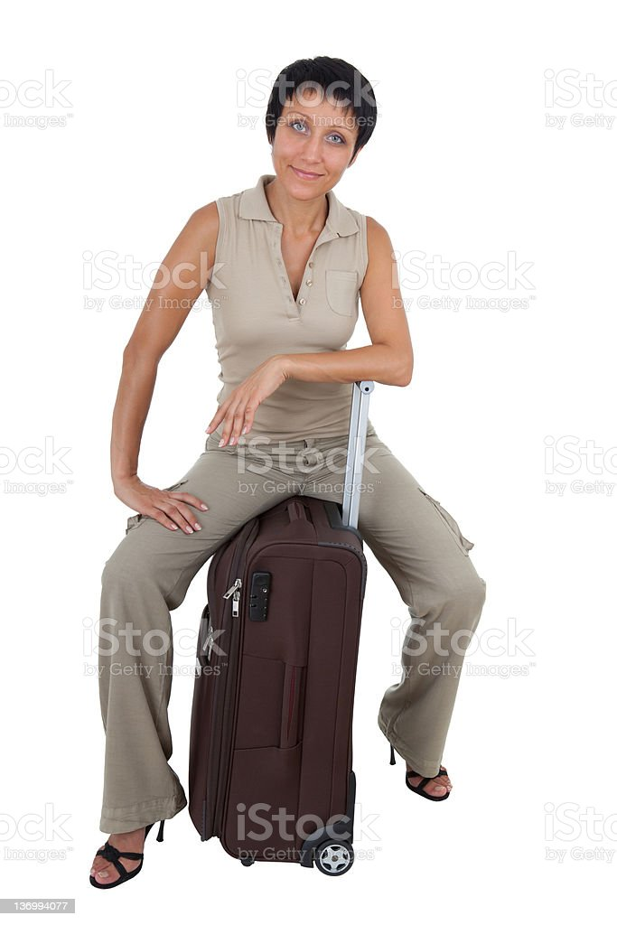 Young tourist woman sits on the  brown traveling suitcase isolat royalty-free stock photo