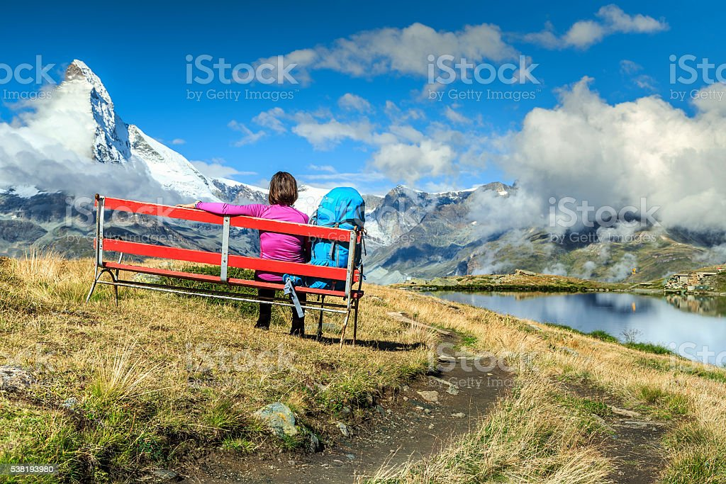 Young tourist woman with backpack relaxing on bench stock photo