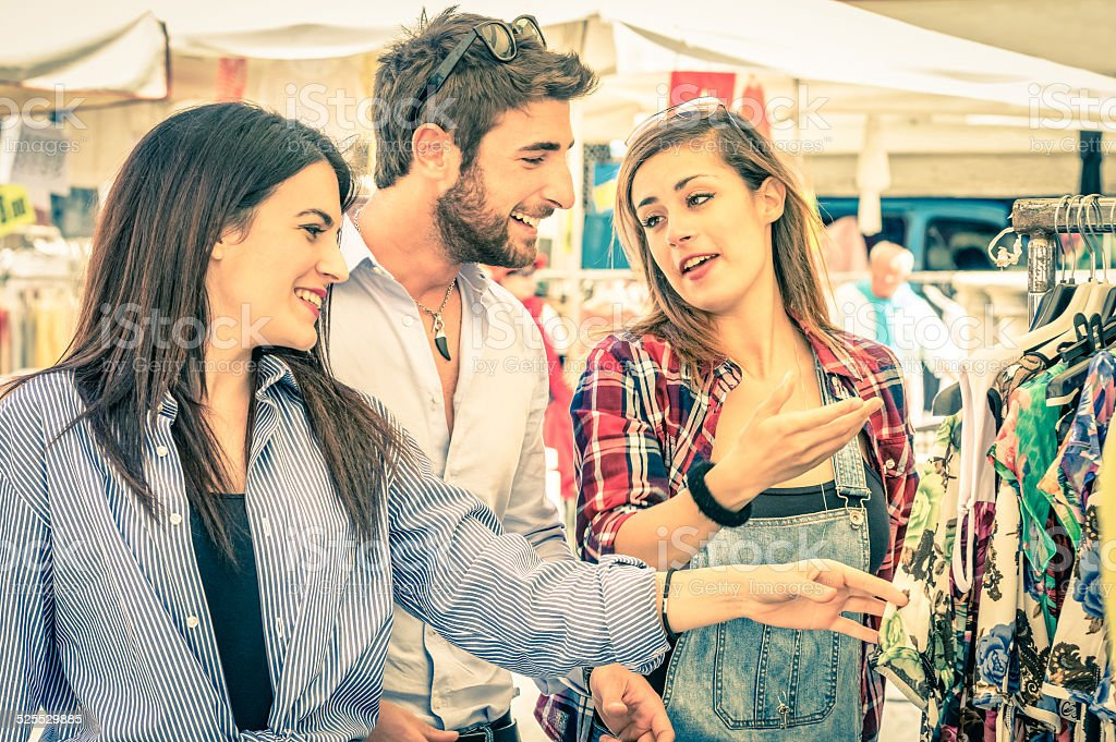 Young tourists friends shopping at the weekly cloth market stock photo