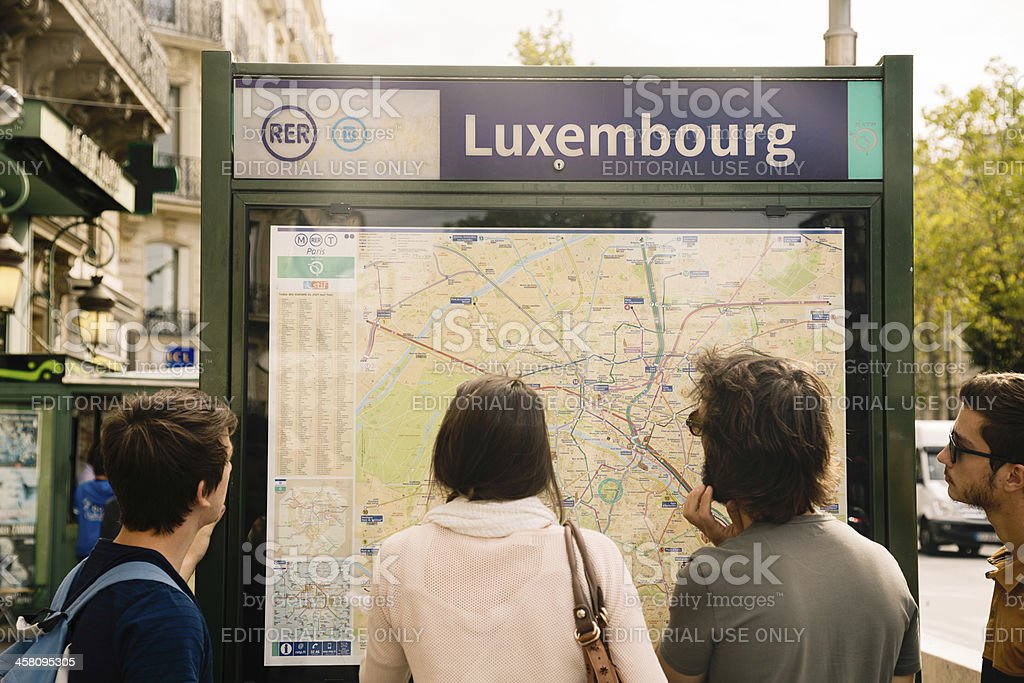 Young tourists looking at Paris map royalty-free stock photo