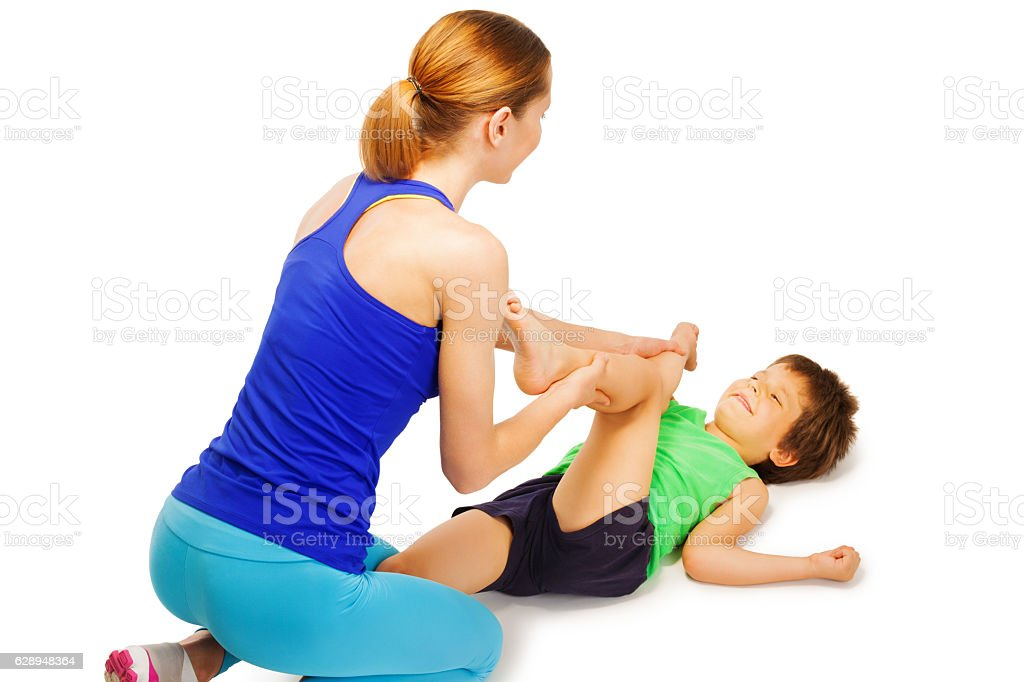 Young trainer helping boy crossing knees to elbows stock photo