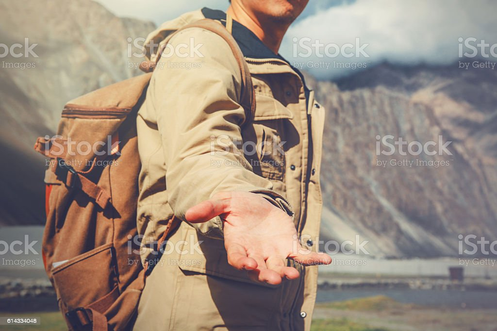 Young travel man lending a helping hand in mountain stock photo