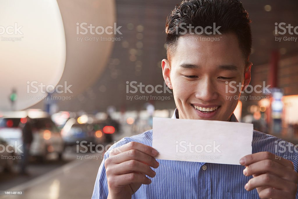 Young traveler looking at ticket in airport royalty-free stock photo