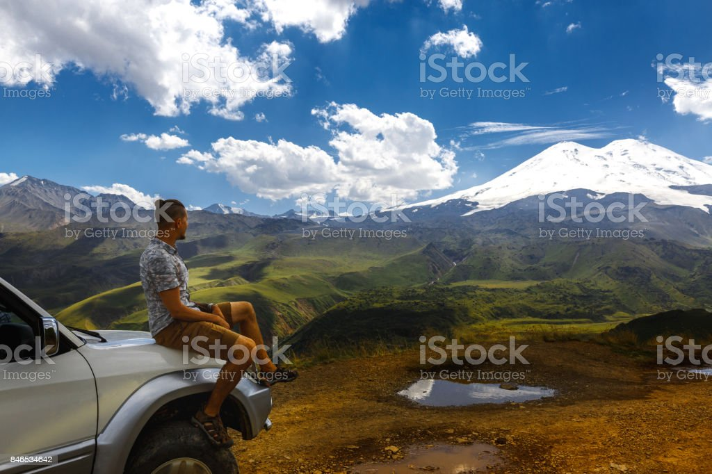 Young Traveler Man Sits On Car And Enjoys View Of Mountains In Summer. Elbrus Region, North Caucasus, Russia stock photo