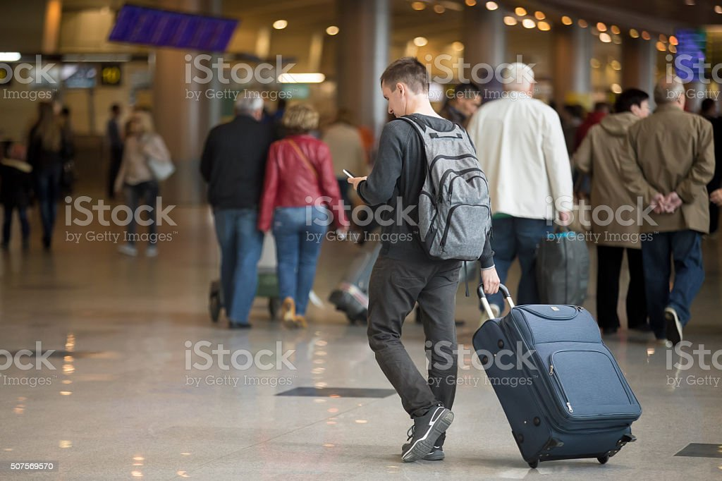 Young traveler with smartphone in airport stock photo