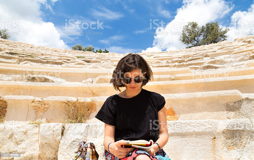 Young Traveler Woman Reading History Of Ancient Theatre stock photo