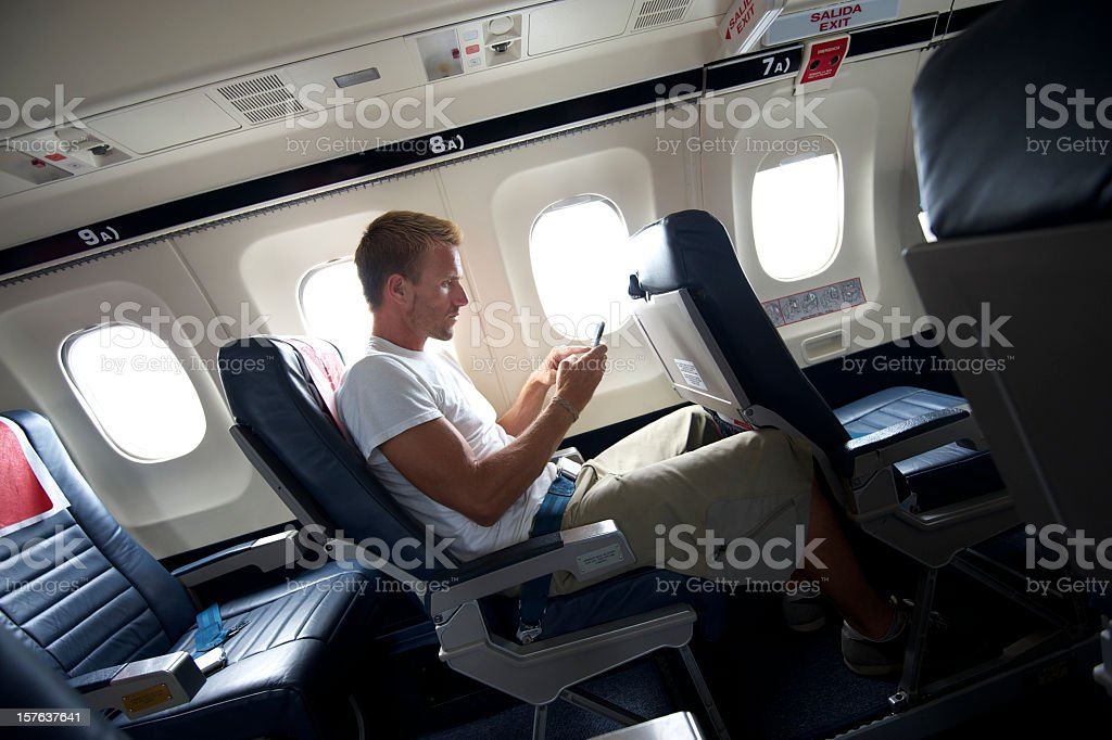 Young Traveling Man Sitting Texting on Airplane Seat royalty-free stock photo