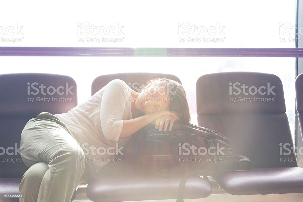 young traveller taking a nap while waiting her flight stock photo
