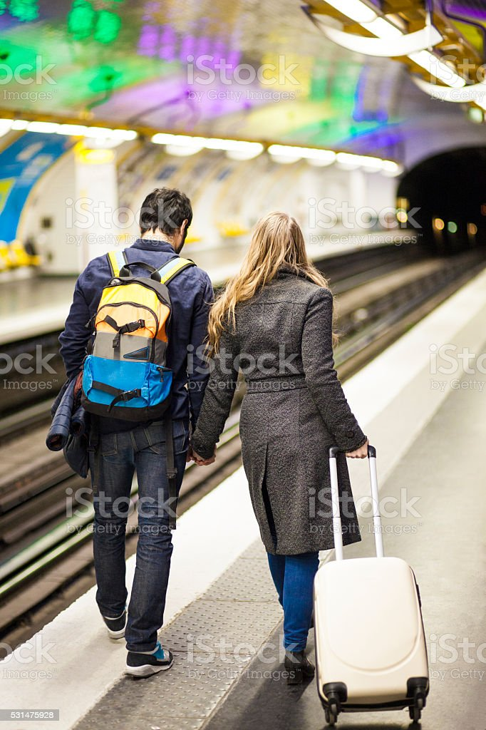 Young Travelling Couple Walking By The Subway Tracks stock photo