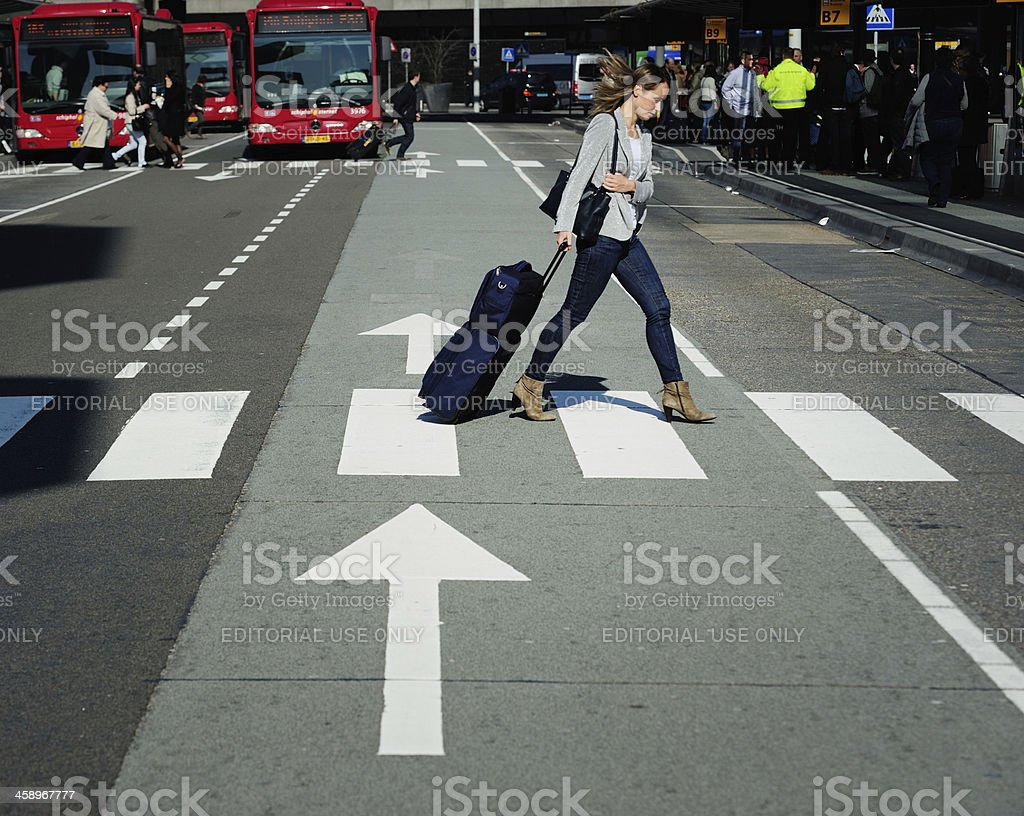 Young travelling woman crossing street with arrows stock photo