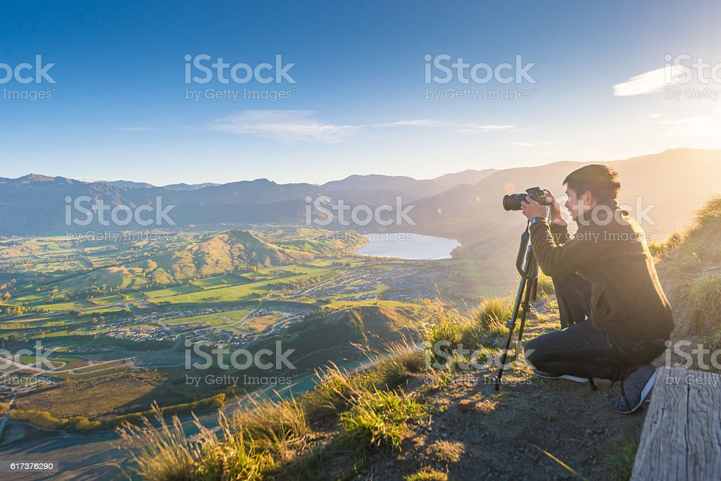 Young travler taking photo at queen town  in new zealand stock photo