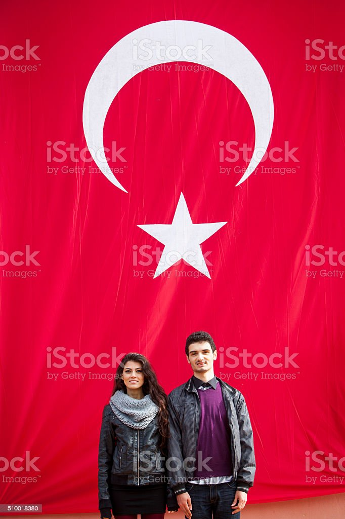 Young Turkish Civilians In Front Of The Turkish Flag stock photo