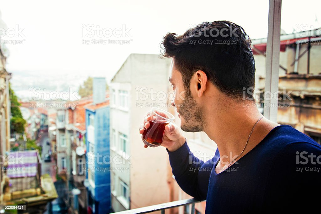 Young Turkish man drinks tea while looking down his street stock photo