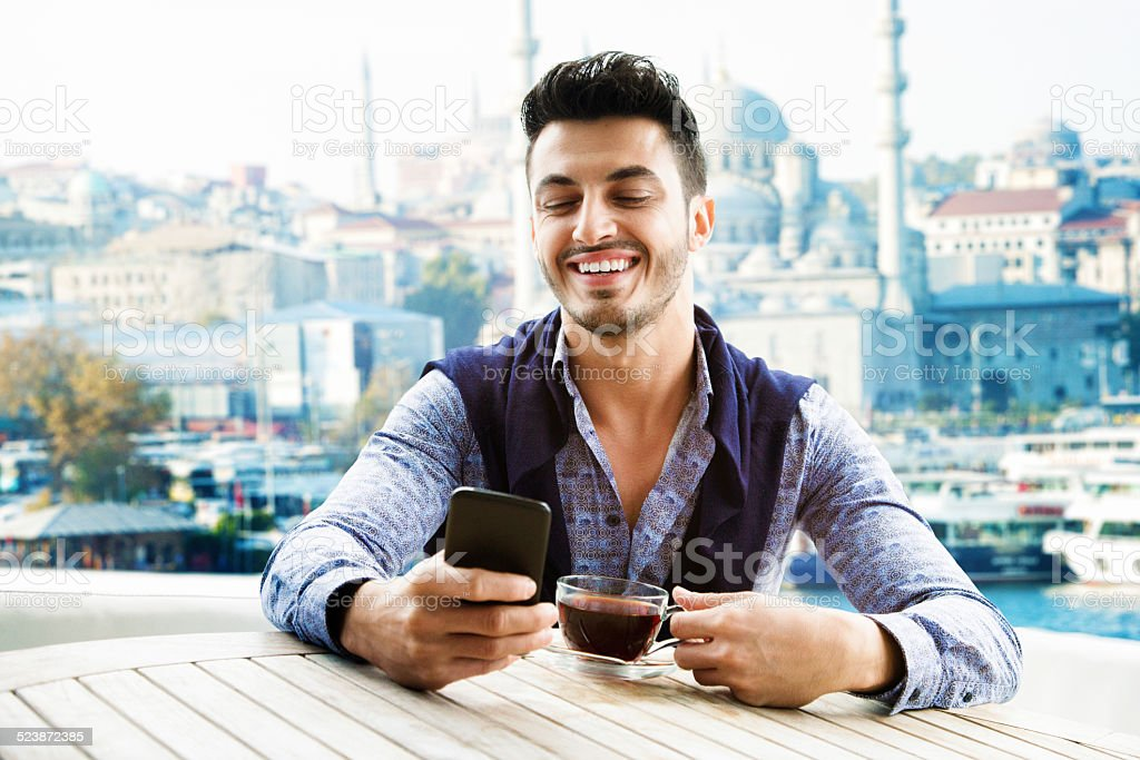 Young turkish man laughs while social networking on his yacht stock photo
